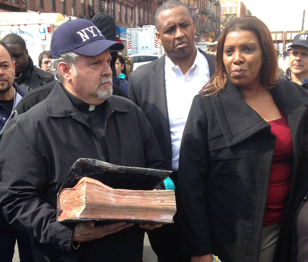Rick Del Rio, pastor of Abounding Grace church in Manhattan, and New York City Public Advocate Letitia James display a damaged but intact Bible they said was recovered from the rubble of the Spanish Christian Church.