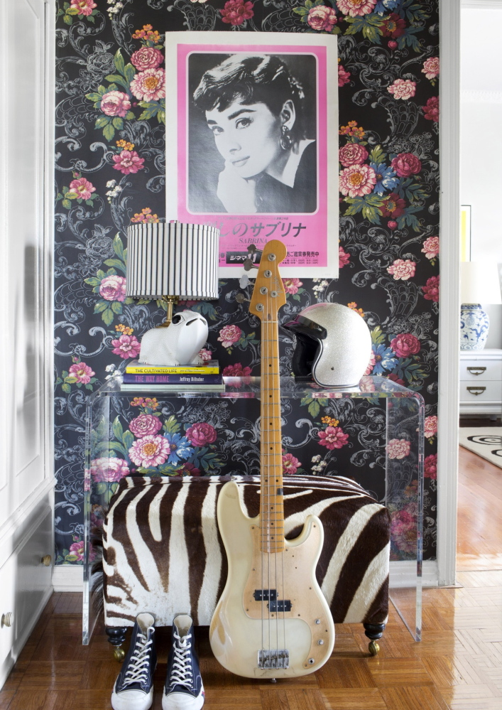 """Floral wallpaper is contrasted with modern furniture and unexpected accessories like a bike helmet and a vintage Japanese poster for the movie """"Sabrina,"""" to create a fresh and edgy look."""