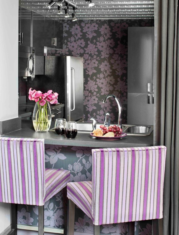An industrial loft kitchen is updated using floral wallpaper with modern scale and colors. The trick to using florals in fresh ways is to choose over-scale botanical fabrics rather than traditional florals with small pattern repeats.