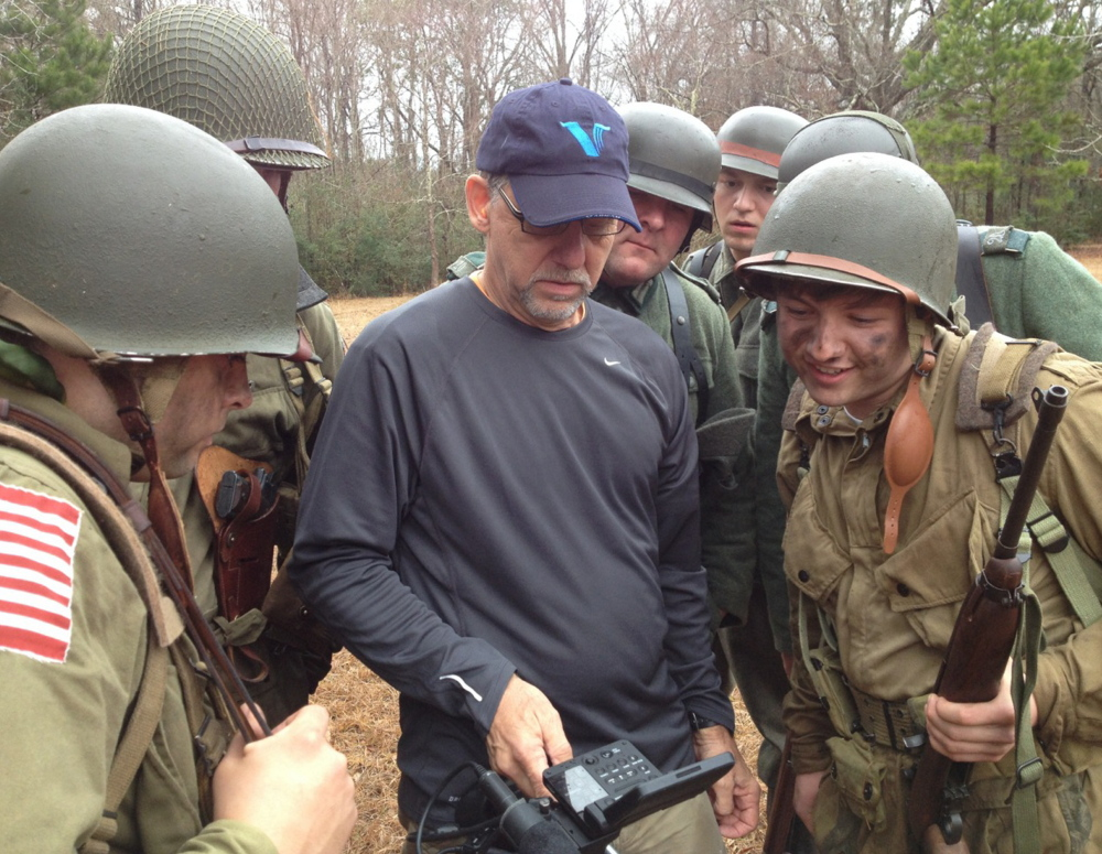 Director of photography Jerry Hattan reviews footage with re-enactors portraying American troops on D-Day.