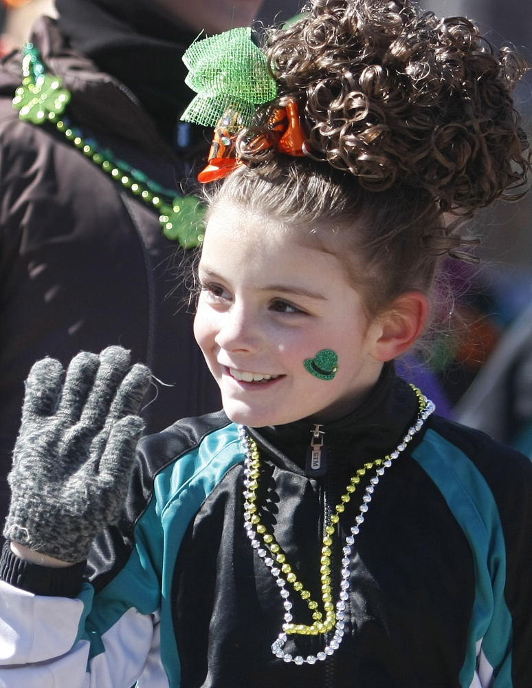 Ava Williams, 7, waves hello to the crowd while performing with the Stillson School of Irish Dance.