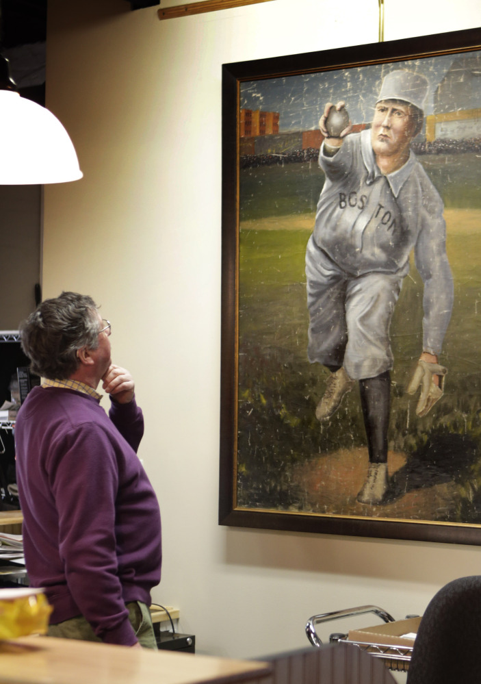 Auctioneer Floyd Hartford examines a 1910 painting of Cy Young in the uniform of the Boston Americans at the Saco River Auction House in Biddeford on Tuesday.