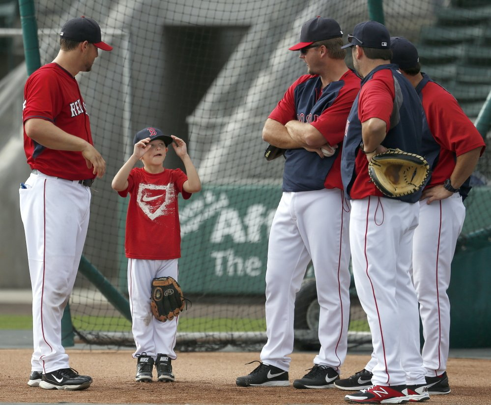 Austin Pierzynski, center left, son of Red Sox catcher A.J. Pierzynski, right, tries on his hat before Red Sox batting practice in Fort Myers, Fla., Monday.