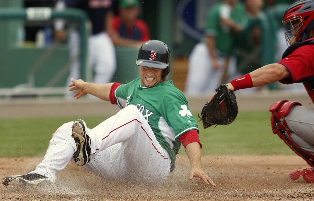 Daniel Nava of the Boston Red Sox evades the tag from St. Louis catcher Tony Cruz during a spring training game versus the St. Louis Cardinals in Fort Myers, Fla., Monday.
