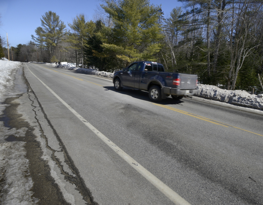 A pickup truck passes the scene along Route 117 in Paris where 16-year-old Xavier Fuentes from Turner was killed on Saturday night.