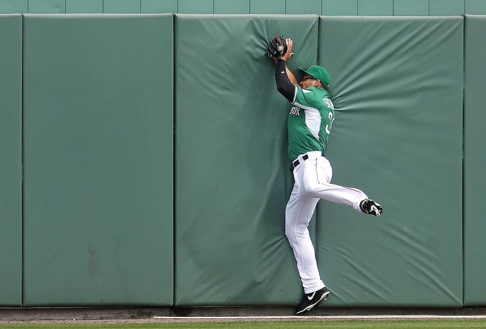 Boston Red Sox outfielder Grady Sizemore slams into the center field wall but holds on to make the catch during a spring training game versus the St. Louis Cardinals on Monday.
