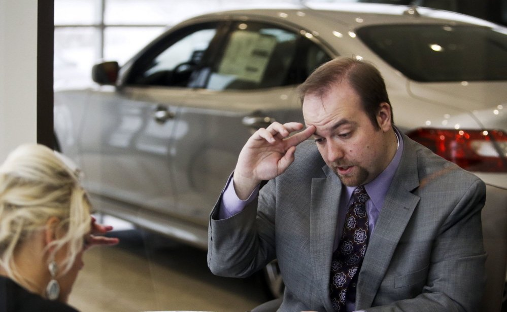 """Morgan Moore, right, has a law degree and $80,000 in debt but works as a salesperson at a car dealership in Golden Valley, Minn. Shown here talking with a customer, Moore says the bearish jobs market has resulted in """"a lost three or four years"""" for his generation."""