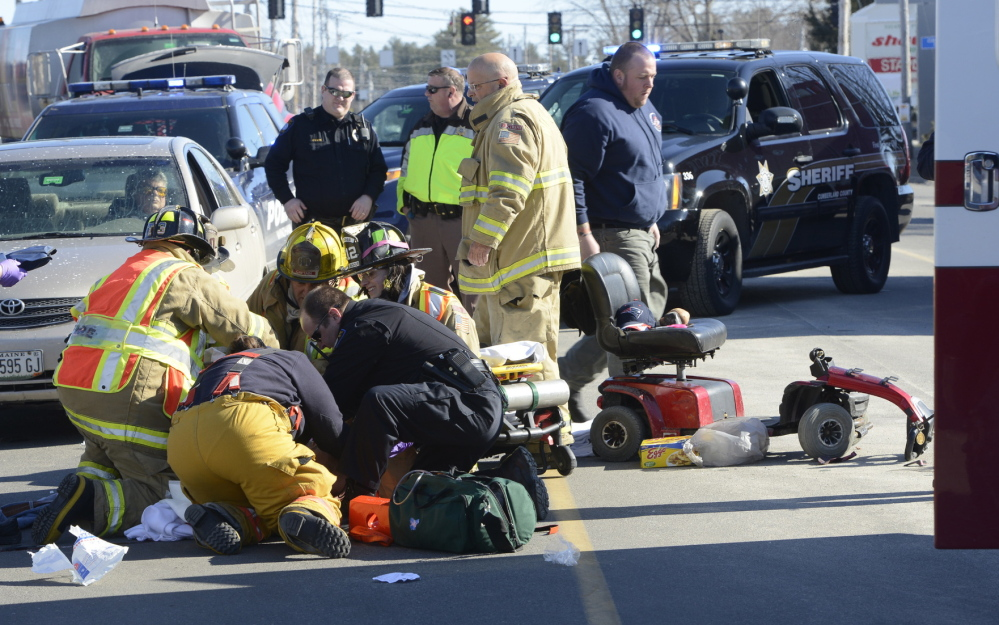 Windham fire and rescue personnel stabilize a man who was hit by a car as he tried to cross Route 302 while riding on an electric scooter in front of a shopping center.