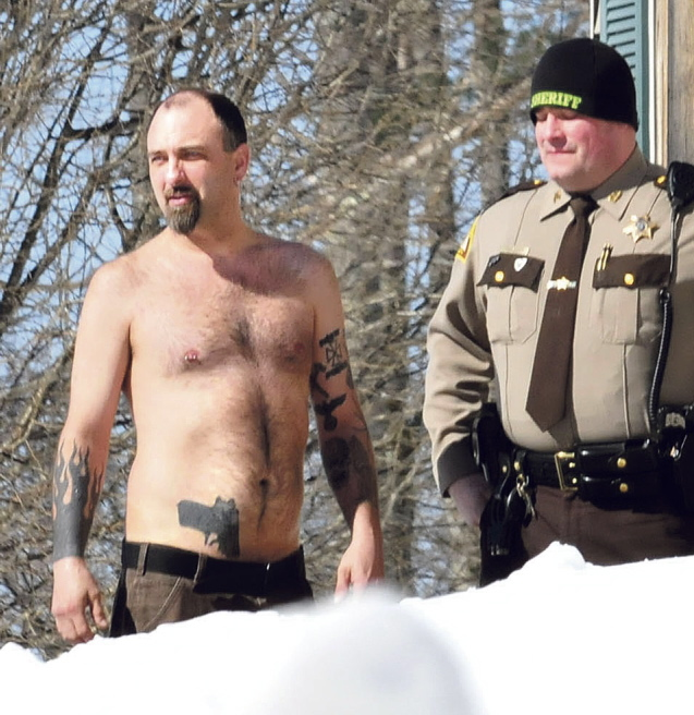 Norridgewock resident Michael Smith, with a tattoo of a gun at his waistband, stands beside a Somerset County sheriff's deputy Tuesday morning.