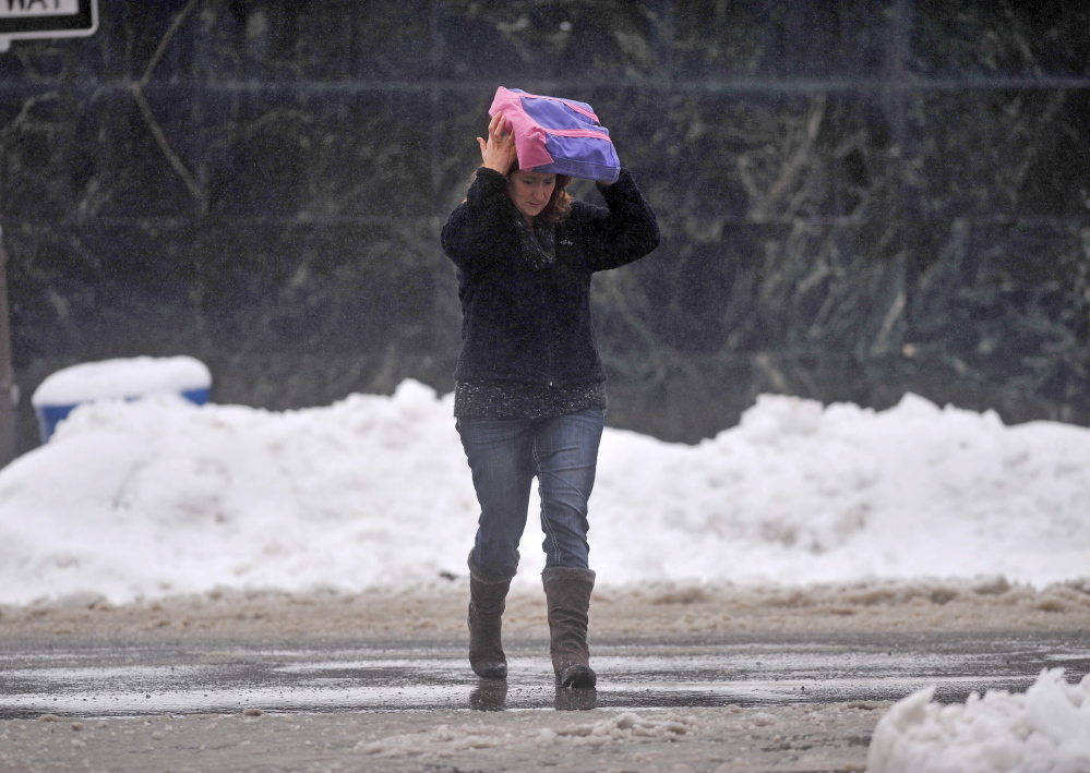 SPRING STORM: A pedestrian covers her head with a bag as she crosses Main Street in Waterville on Thursday.