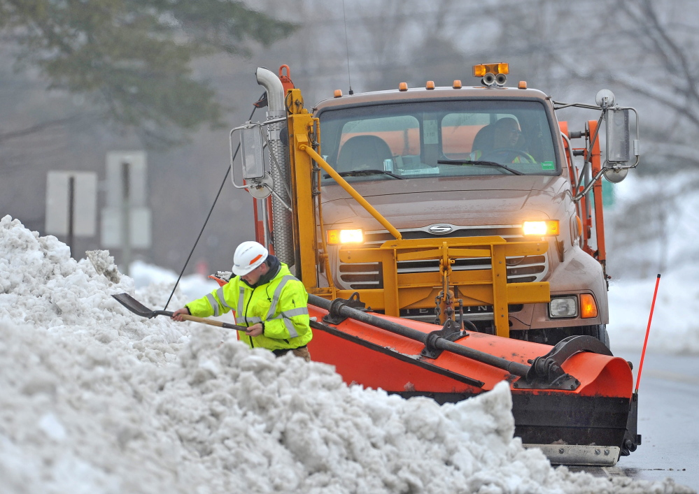 Drew Veilleux with the Maine DOT shovels snow from the side of Route 201 in Hinkley with his plow waiting behind him Thursday. Crews worked to help with drainage issues.