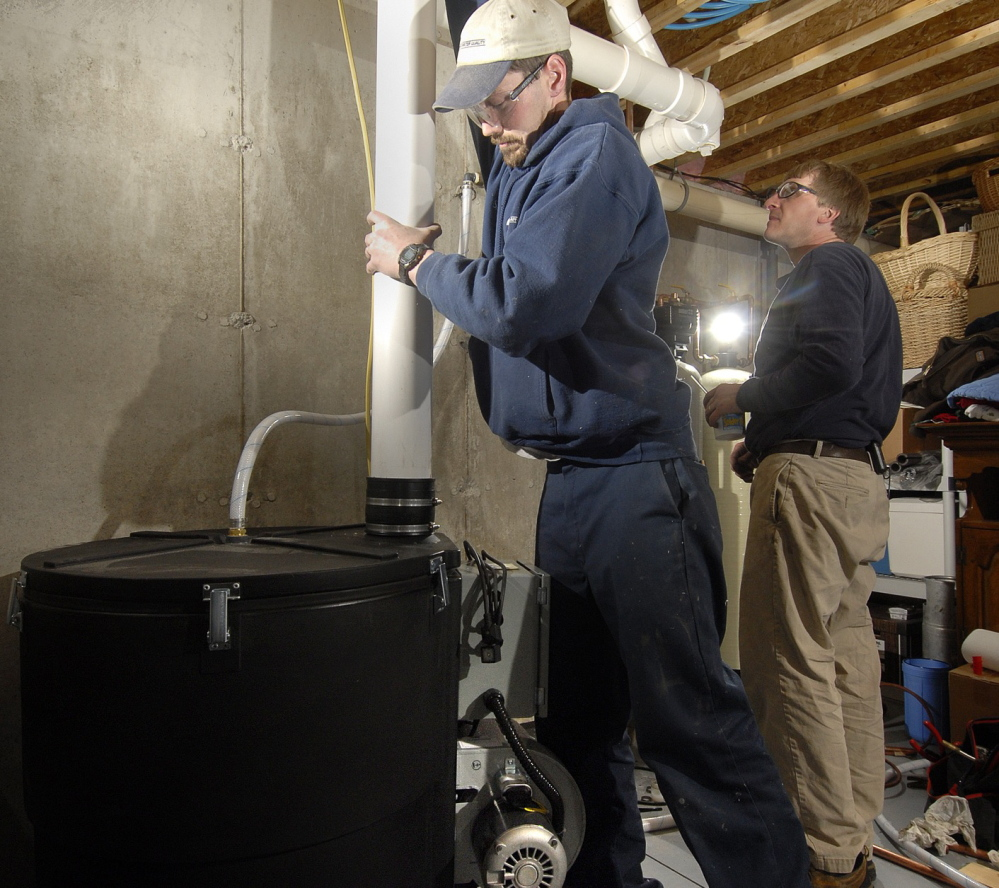 Shawn Garrity, left, and Scott King of Air & Water Quality, Inc. of Freeport install a radon gas treatment unit in a Maine home in 2007. Maine law requires landlords to test for radon in all buildings with rental units – but it's still unclear what agencies will enforce the penalties if they don't.