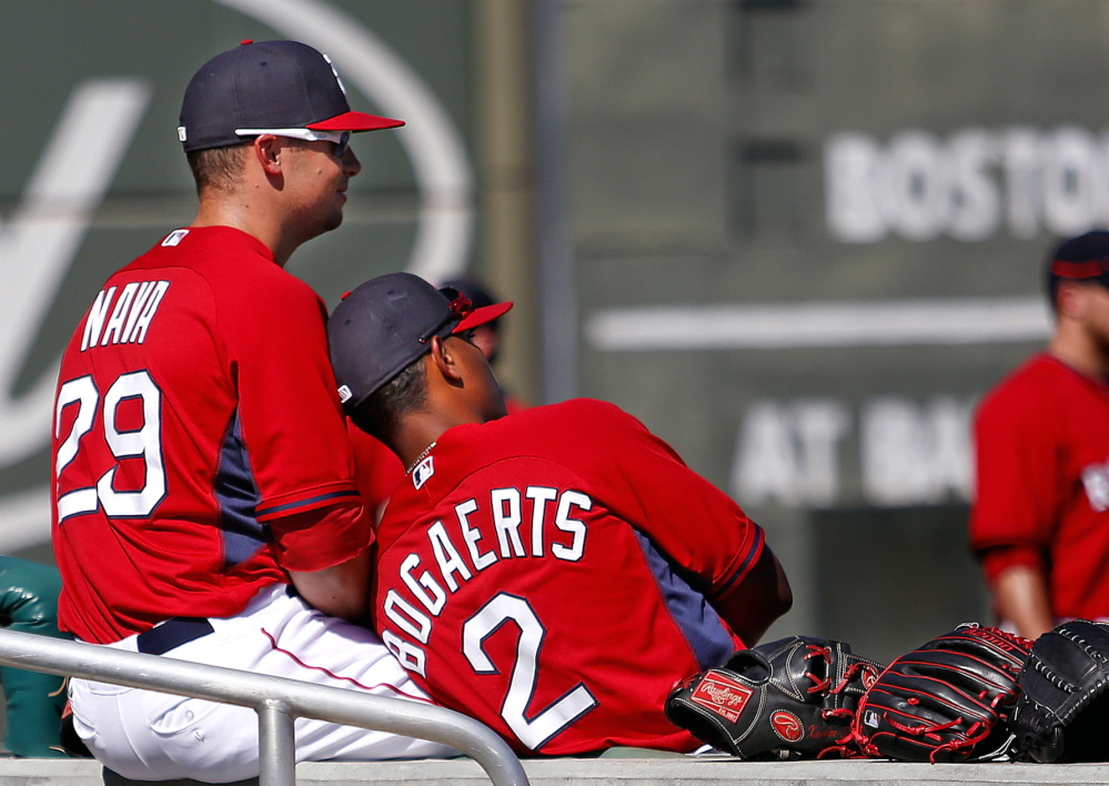 """Daniel Nava and Xander Bogaerts take a break before a spring training game at JetBlue Park last Thursday. Of last year's champions, Manager John Farrell said: """"That was the closest team I've been around in 30 years of professional baseball."""""""