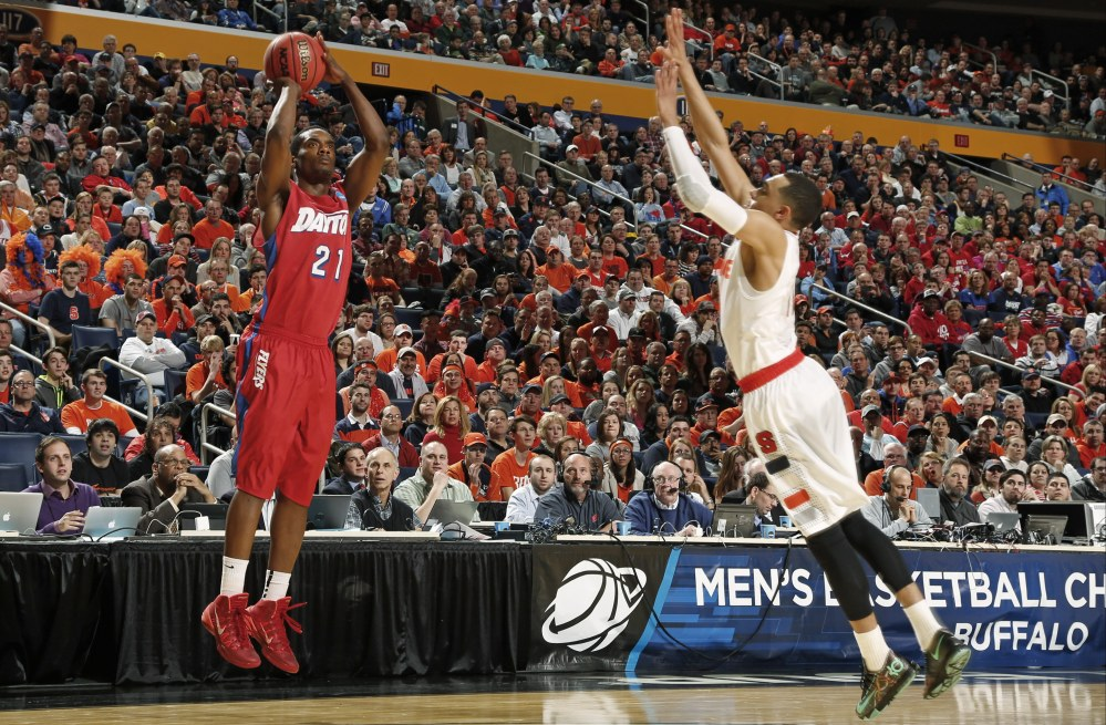 Dayton's Dyshawn Pierre (21) shoots over Syracuse's Tyler Ennis (11) during the first half of a third-round game in the NCAA men's college basketball tournament in Buffalo, N.Y., Saturday.