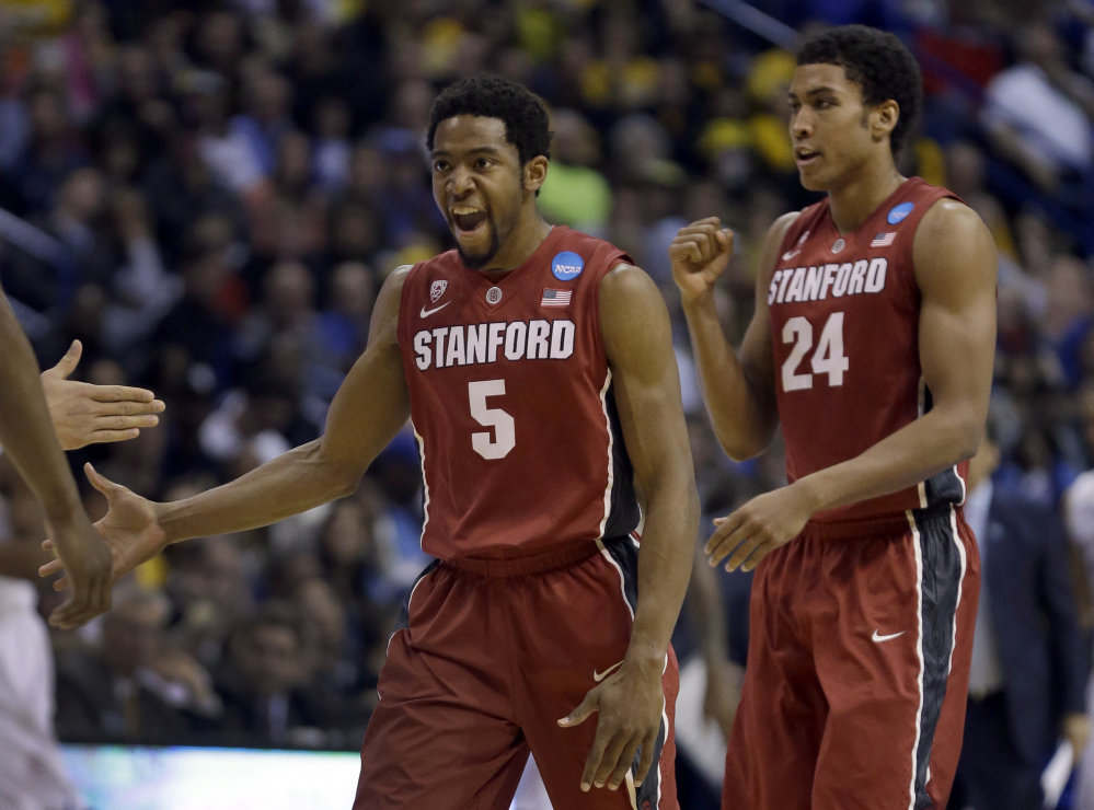 Stanford's Chasson Randle, left, and Josh Huestis celebrate during the second half of Sunday's third-round game against Kansas in the NCAA tournament in St. Louis. Stanford, seeded 10th, knocked off No. 2 Kansas to reach the Sweet 16.