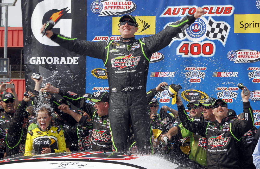 Kyle Busch, center, celebrates, in the victory circle after winning the NASCAR Sprint Series auto race in Fontana, Calif., on Sunday.