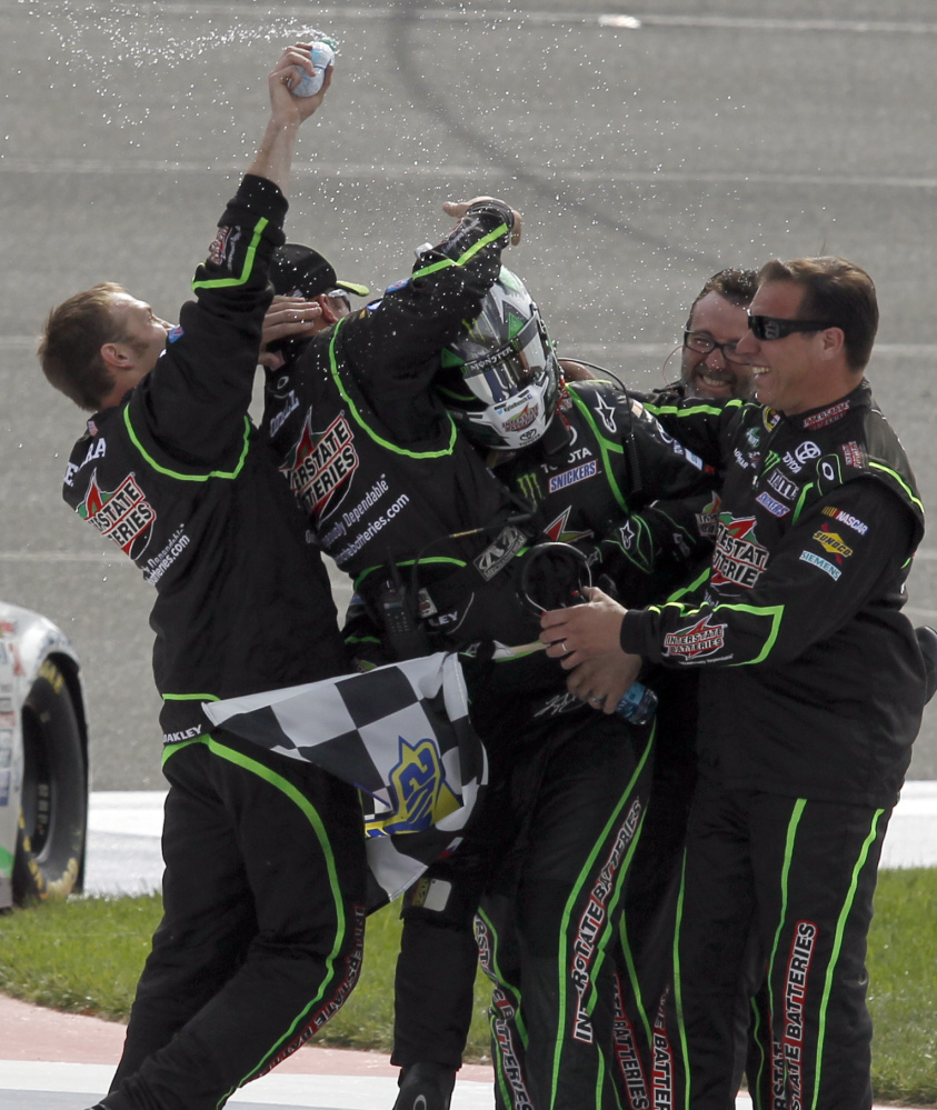A helmeted Kyle Busch finds himself the center of attention as members of team celebrate after his first-place finish at Fontana, Calif., on Sunday.