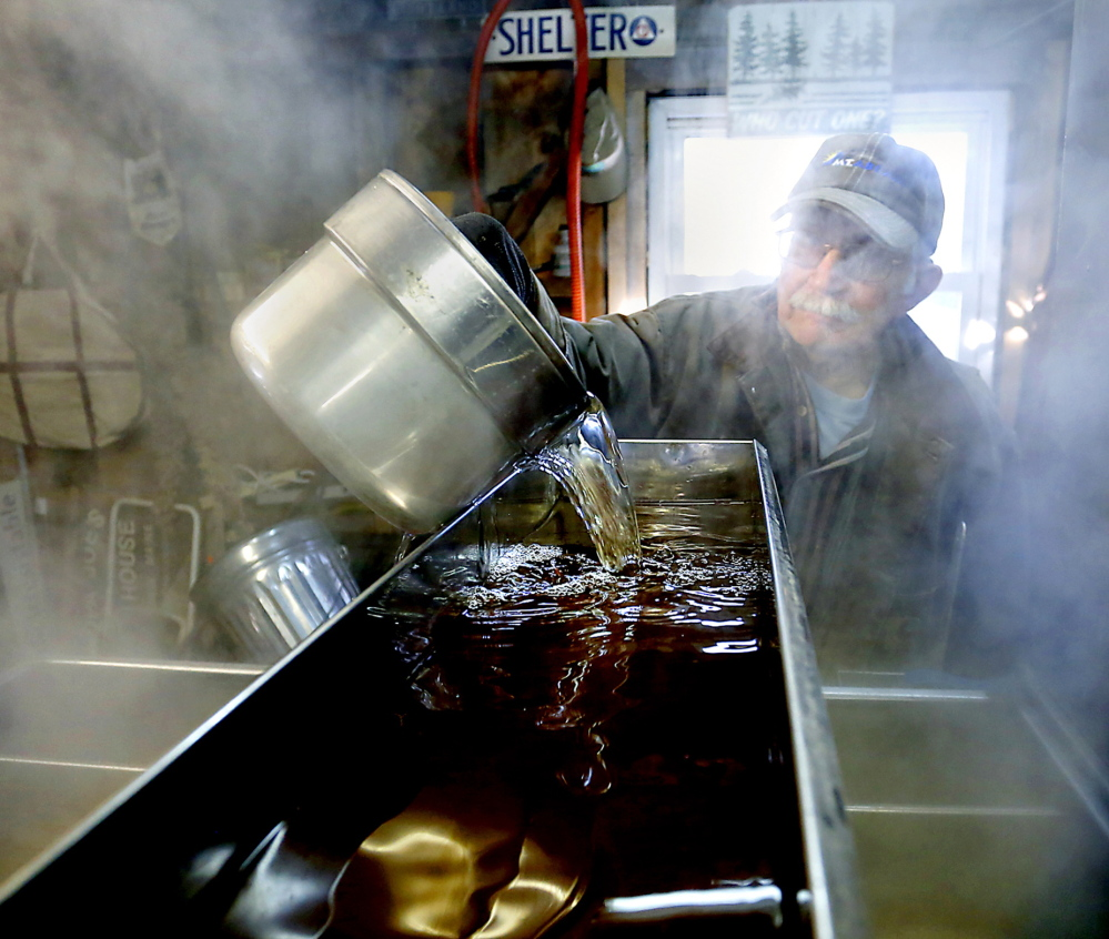 At Grandpa Joe's Sugar House in Baldwin, Steven McKenney pours sap into a pan that rests on the wood-fired evaporator.