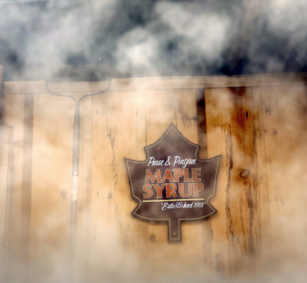 Steam from a wood-fired evaporator surrounds a sign hanging in a sugar house at Pingree Maple Products in Cornish during Maine Maple Sunday. As the water evaporates from the sap, what's left gets thicker and sweeter.
