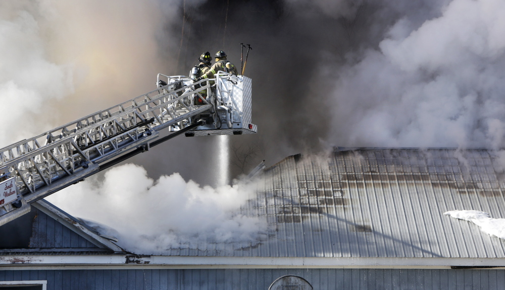 Windham firefighters direct water through the roof of Town & Country Cabinets in Gorham on Tuesday. The fire may have started around an exhaust fan on the second floor, where smoke was initially spotted, said Gorham Fire Chief Robert Lefebvre.