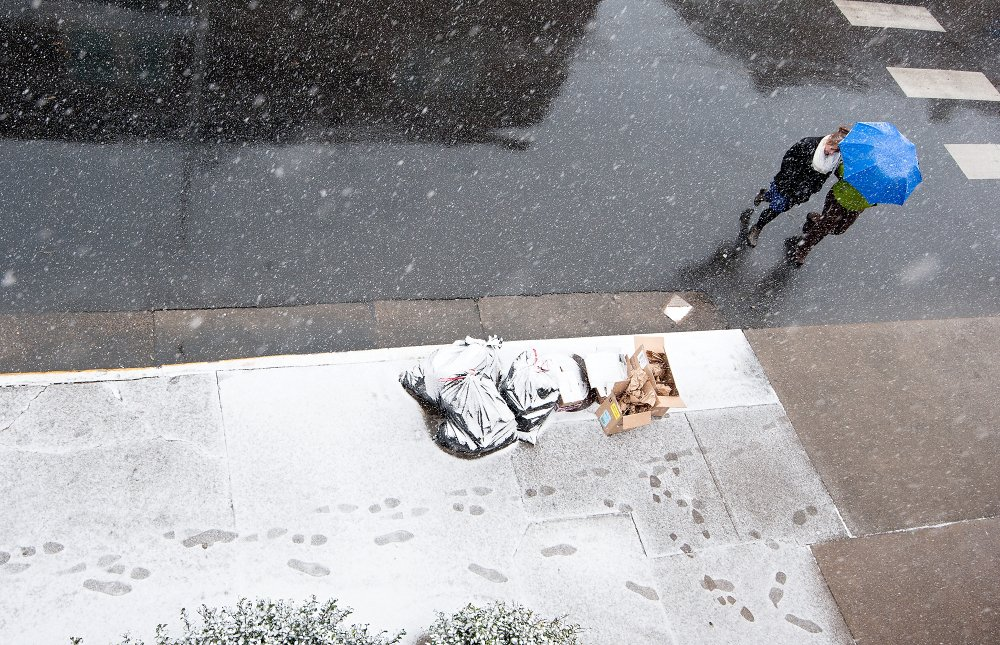 Snow falls as pedestrians cross the street Tuesday in Harrisonburg, Va. The National Weather Service says a powerful low-pressure system will develop off the mid-Atlantic coast Tuesday night.