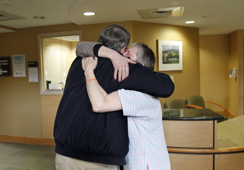 Nurse Debbie Little, right, and retired internist Erwin Steubner hug after the unexpected announcement Tuesday of the closure of the North Adams Regional Hospital.