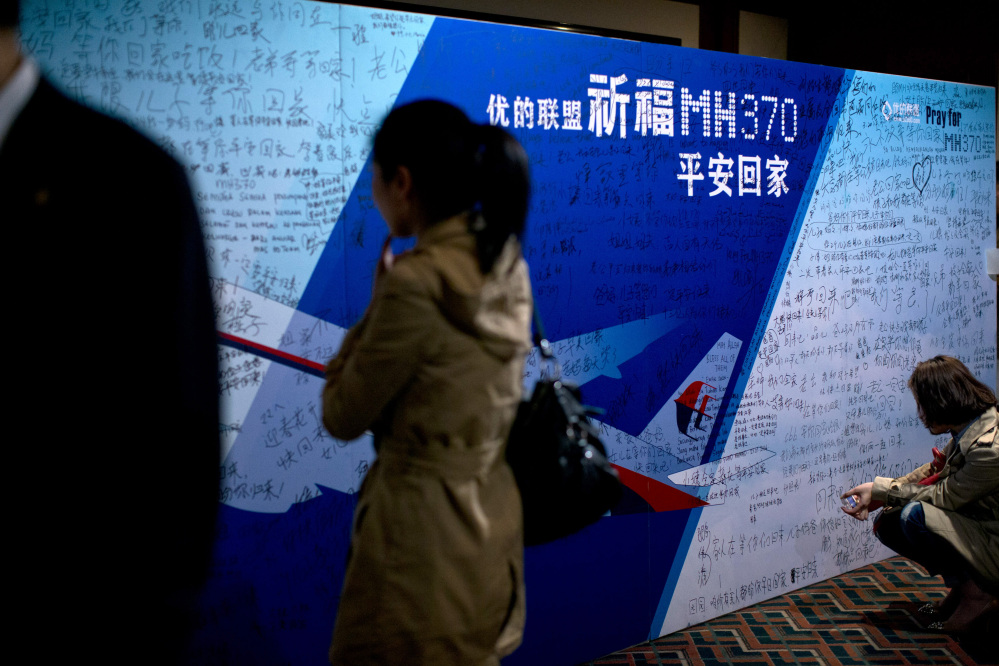 """Journalists read words from board covered by written wishes from relatives during a briefing meeting given by Malaysian officials at a hotel in Beijing, China, Wednesday, March 26, 2014. Some of the wishes read, """"Dear husband, you must stay strong, I am waiting for you. My dear, please be back soon."""" The search of the missing plan resumed Wednesday after fierce winds and high waves forced crews to take a break Tuesday. A total of 12 planes and five ships from the United States, China, Japan, South Korea, Australia and New Zealand were participating in the search, hoping to find even a single piece of the jet that could offer tangible evidence of a crash and provide clues to find the rest of the wreckage."""