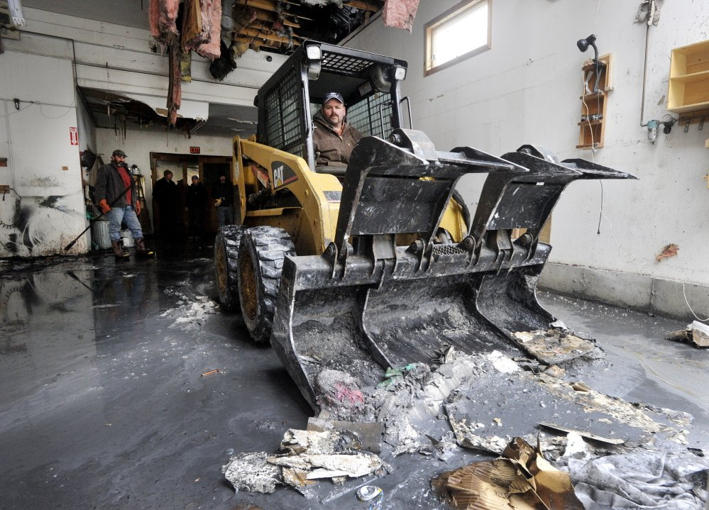 Troy Pride, a friend of business owner David Smith, runs a skid steer Wednesday to clear debris in the partially burned-out building. A structural engineer will survey the damage Thursday and determine whether the 19th-century building can be saved.