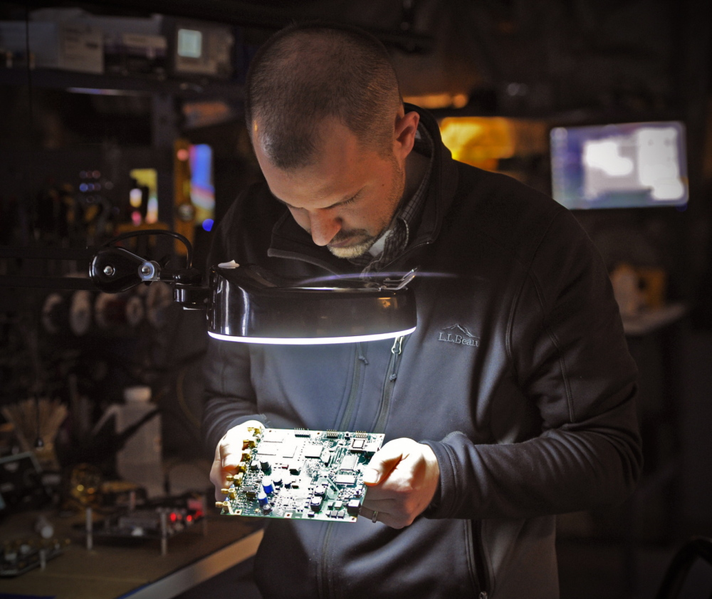 Electronics technician Tom Parker conducts a test on a control board at Fluid Imaging Technologies in Scarborough.