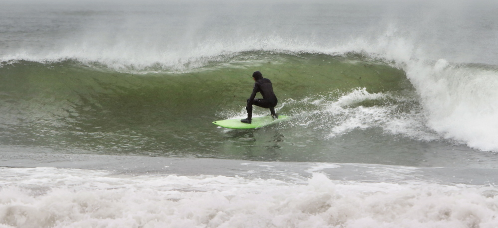 A surfer takes advantage of waves kicked up by a combination of an astronomical high tide and strong northeast winds Sunday at Gooch's Beach in Kennebunk.