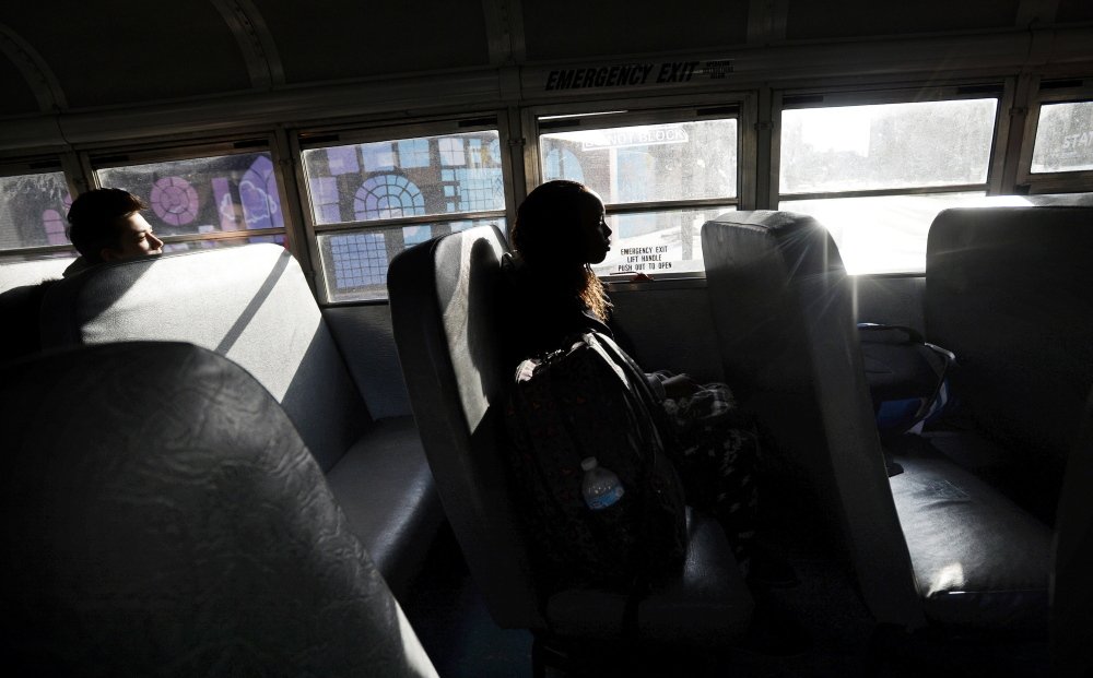 Kera Pingree, 17, left, and Dylantha Musonerwa, 14, ride the late bus home from Deering High School. Several juniors pushed to institute a late bus and found $8,000 in a fund for co-curricular activities to pay for the bus three days a week as a pilot project.