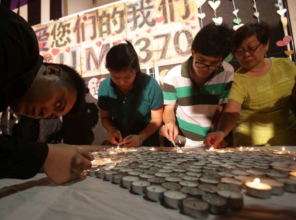 People light candles during a ceremony for the passengers on board the missing Malaysia Airlines flight MH370 in Kuala Lumpur, Malaysia, Sunday.