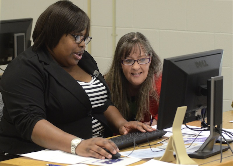 Quetta Pipkin, left, of the Medical Foundation of Chattanooga, assists Paige Carlton during an Affordable Care Act health care enrollment event at Cleveland State Community College, Wednesday, March 26, 2014, in Cleveland, Tenn.