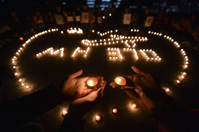 University students in Yangzhou, in eastern China's Jiangsu province, hold a candlelight vigil on March 13 for passengers on the missing Malaysia Airlines Flight MH370.