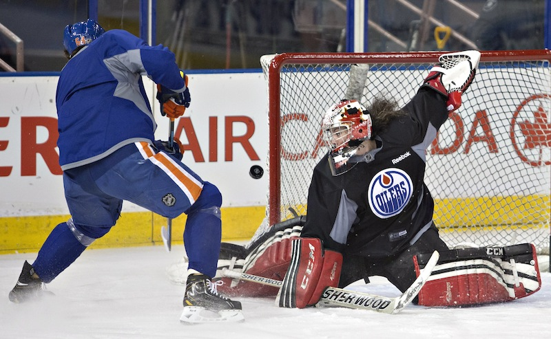 Canadian Olympic women's team goalie Shannon Szabados makes a save on Nail Yakupov as she takes part in the the Edmonton Oilers NHL hockey practice in Edmonton, Alberta, on Wednesday.