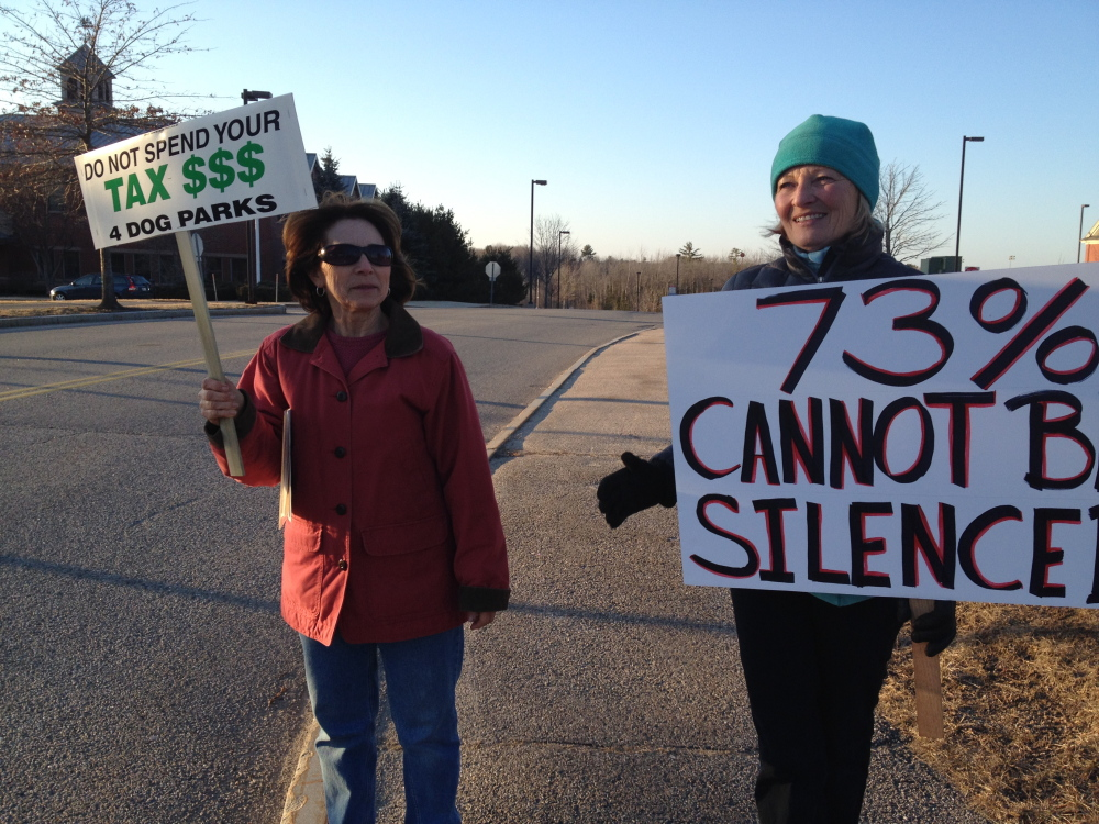 Kris Poore and Maureen Burns were among 20 protesters in front of Scarborough Town Hall Wednesday night opposed to proposed dog restrictions on town beaches.