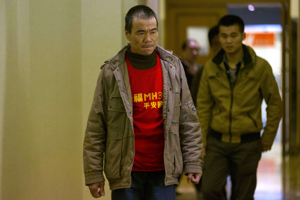 "A relative of Chinese passengers onboard Malaysia Airlines Flight 370 wears a t-shirt which reads ""Pray for MH370 safe return"" as he arrives to attend a closed door meeting with Malaysian officials via teleconference at a hotel in Beijing, China, Wednesday, April 2, 2014. A Malaysian police investigation into the pilots of the missing Malaysian jet might turn up nothing, the force's chief said Wednesday, while the head of the international search effort also acknowledged that an air hunt to spot wreckage on the surface of the southern Indian Ocean was not certain of success."