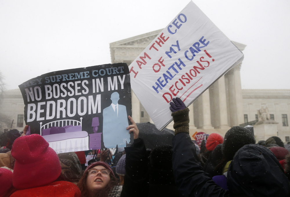 Demontrators gather in front of the Supreme Court in Washington last month as the court heard oral argument in the challenges of President Barack Obama's health care law requirement that businesses provide their female employees with health insurance that includes access to contraceptives. The Associated Press