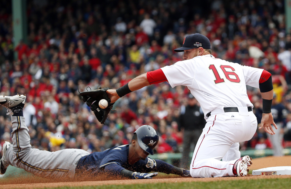 Milwaukee Brewers' Jean Segura slides in safely with a triple as Boston Red Sox third baseman Will Middlebrooks (16) takes in the throw from left field during the first inning of a baseball game at Fenway Park in Boston on Friday.