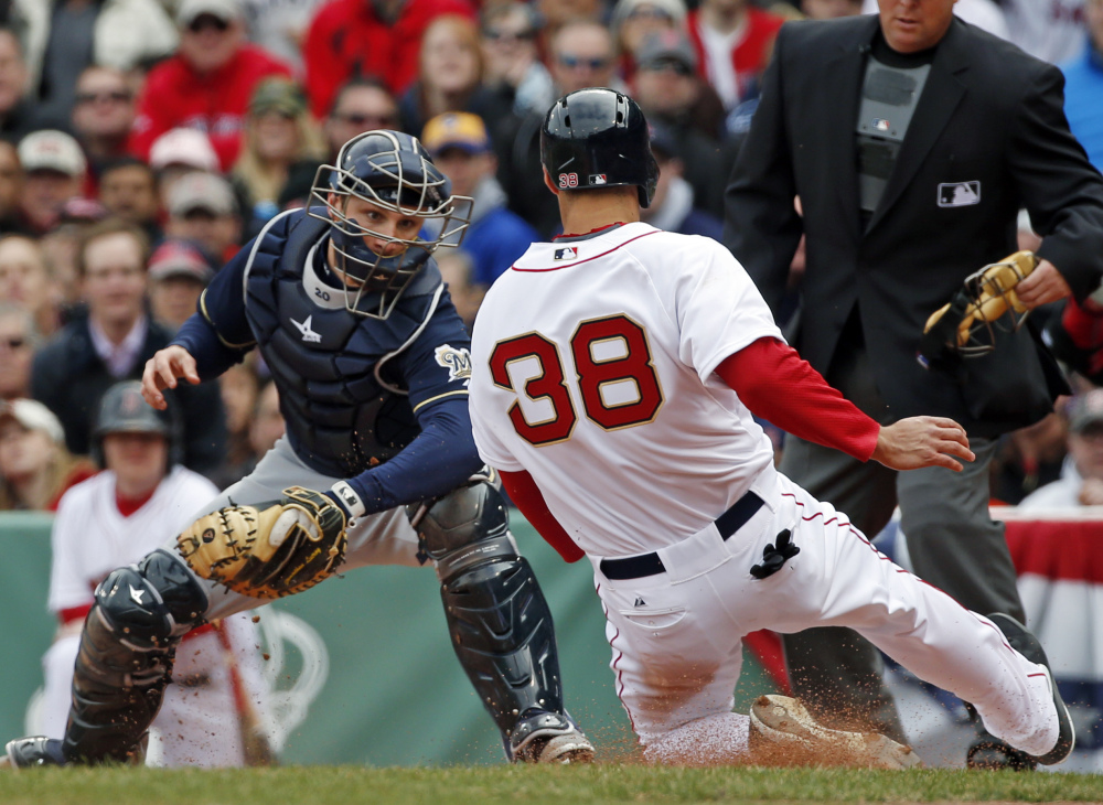 Milwaukee Brewers catcher Jonathan Lucroy prepares to tag out Boston Red Sox's Grady Sizemore trying to score on a sacrifice fly during the second inning at Fenway Park in Boston on Friday.