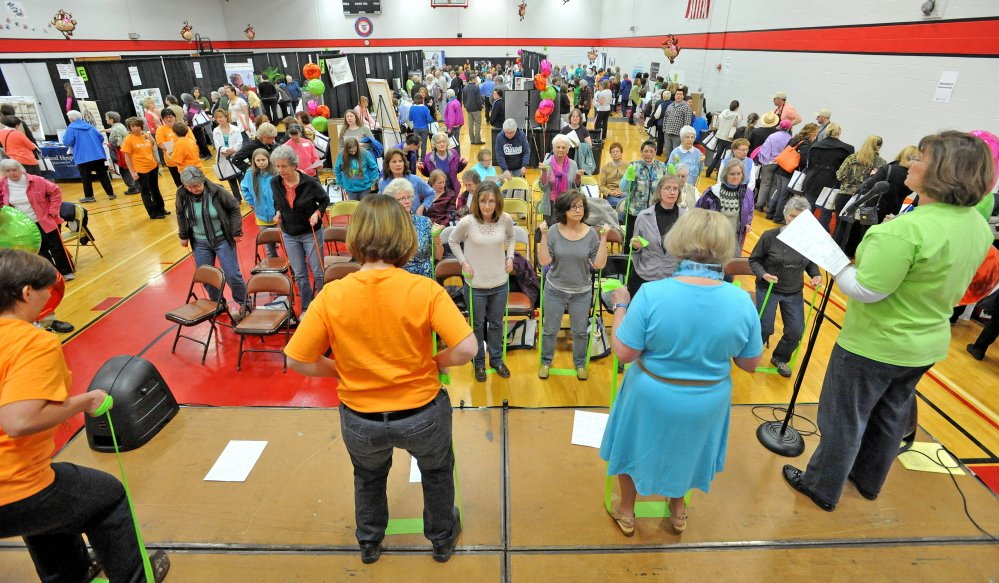Women watch and participate in an elastic band exercise demonstration Saturday at the 17th annual World of Women's Wellness, sponsored by Inland Hospital at Thomas College.