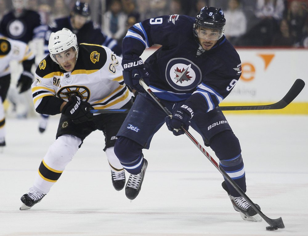 Boston Bruins' Brad Marchand chases down Winnipeg Jets' Evander Kane during the second period of Thursday's NHL game in Winnipeg, Manitoba.