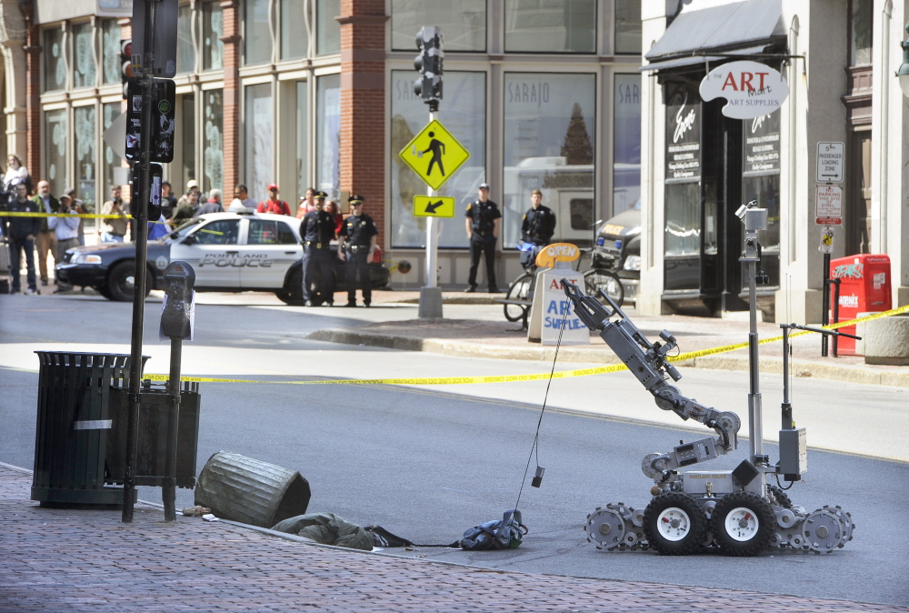 A Portland police bomb squad robot retrieves a device used in a robbery Friday morning from a trash can at the CVS drugstore at 510 Congress St.