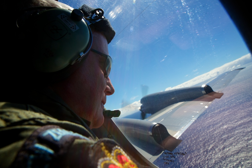Sgt. Trent Wyatt, a crew member of a Royal New Zealand Air Force P-3 Orion, is tasked with visually searching for aircraft debris as the plane flies at 800 feet on Friday.