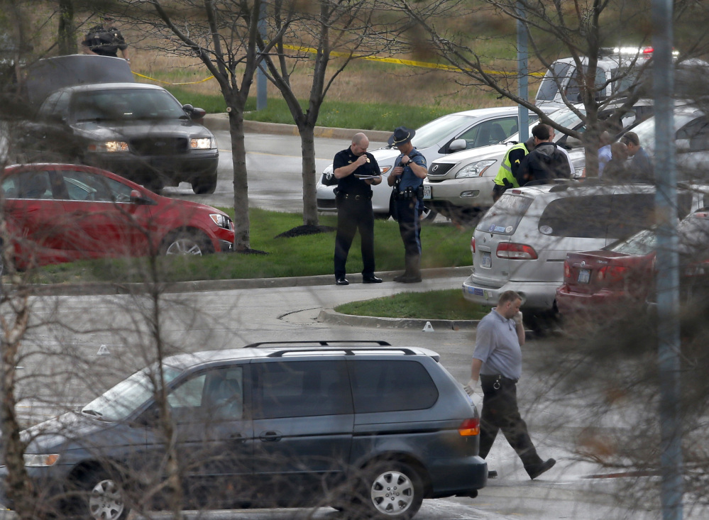 Investigators work behind a police line near the location of a shooting at the Jewish Community Center in Overland Park, Kan., Sunday.