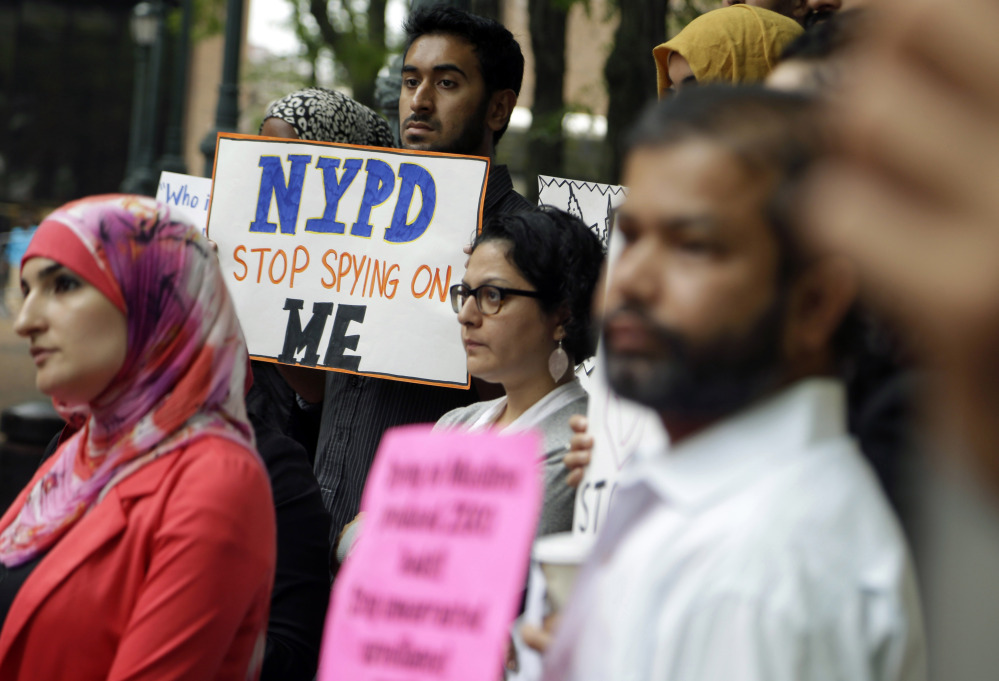 A group of people hold signs protesting the New York Police Department's program of infiltrating and informing on Muslim communities during a rally near police headquarters in New York in August. The department announced Tuesday that the unit has been disbanded.
