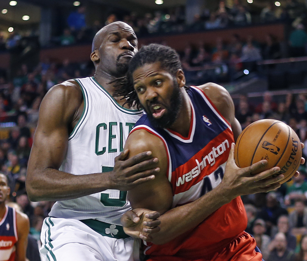 Wizards forward Nene Hilario drives against Boston center Joel Anthony in Wednesday night's game at Boston. The Wizards won to clinch the fifth playoff seed in the Eastern Conference.