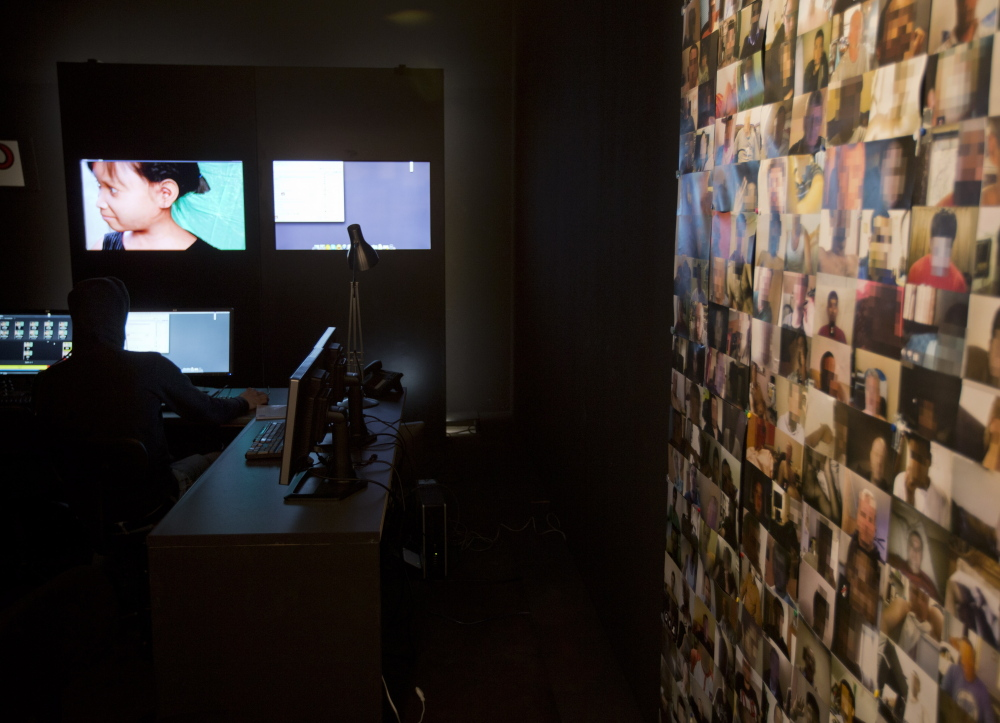 An investigator fishes for pedophilia suspects near a wall plastered with pictures of men who have sought out Sweetie, a computer generated image, at left.