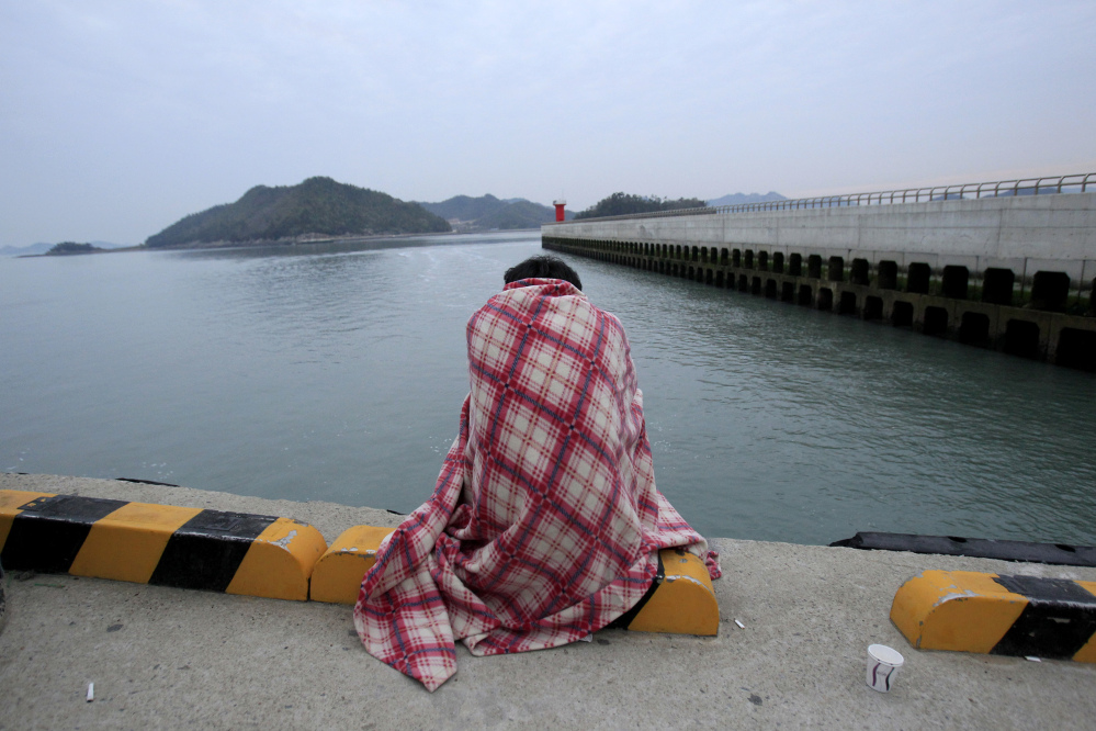 A relative waits for their missing loved one at a port in Jindo, South Korea, Wednesday, April 16, 2014. A ferry carrying 459 people, mostly high school students on an overnight trip to a tourist island, sank off South Korea's southern coast on Wednesday, leaving nearly 300 people missing despite a frantic, hours-long rescue by dozens of ships and helicopters.