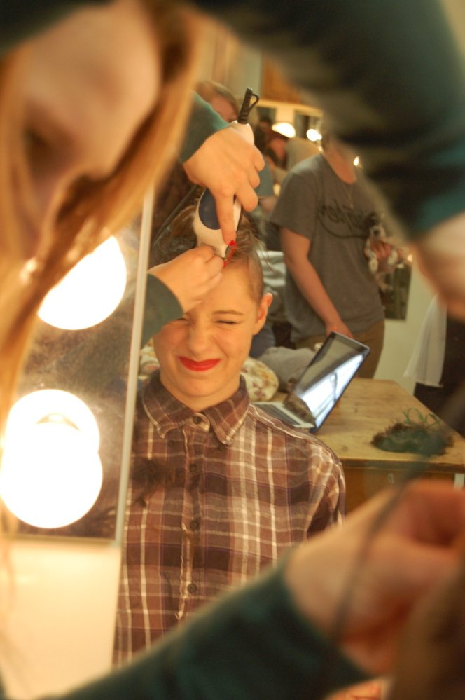 "Clare McKelway grimaces as she shaves her head in preparation for this weekend's opening of ""In the Underworld"" at the USM."